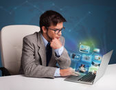 Young man sitting at desk and watching his photo gallery on lapt — Stock Photo