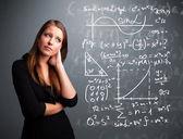 Schöne schulmädchen denken über komplexe mathematische zeichen — Stockfoto