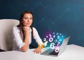 Beautiful young woman sitting at desk and typing on laptop with — Stock Photo