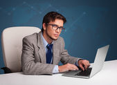Young man sitting at desk and typing on laptop — Foto de Stock