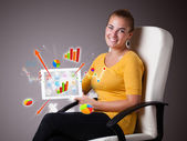Woman holding modern tablet with colorful diagrams and graphs — Photo