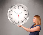 Attractive lady holding a huge clock — Stock Photo