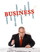Businessman sitting at desk with word cloud — Stock Photo
