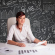 Businesswomsitting at desk with business scheme and icons — Stock Photo #23398334