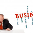 Businesman sitting at desk with business word cloud - Foto Stock