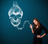 Young woman smoking dangerous cigarette with toxic skull smoke — Foto de Stock
