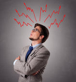 Handsome man thinking with arrows overhea — Stock Photo