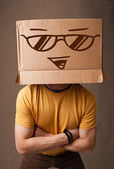 Young man gesturing with a cardboard box on his head with smiley — Stock Photo