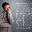 Handsome school boy thinking about complex mathematical signs - Stock Photo