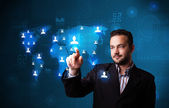 Attractive businessman choosing from social network map — Stock Photo