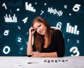 Ung affärskvinna sitter vid skrivbord med diagram och statistik — Stockfoto