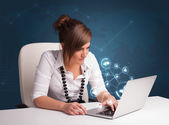 Young lady sitting at desk and typing on laptop with social netw — Stock Photo