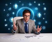 Uomo d'affari seduto alla scrivania con le icone di rete sociale — Foto Stock