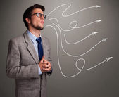 Attractive man looking at multiple curly arrows — Stock Photo
