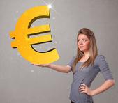 Hermosa chica con un gran cartel de euro oro 3d — Foto de Stock