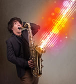 Young man playing on saxophone with colorful sound waves — Stock Photo