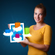 Woman holding modern tablet with colorful shopping bags on cloud - Stock Photo
