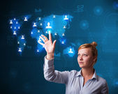 Beautiful businesswoman choosing from social network map — Stock Photo