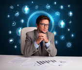 Businessman sitting at desk with social network icons — Stock Photo