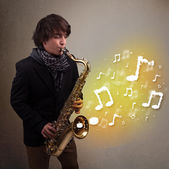 Handsome musician playing on saxophone with musical notes — Photo