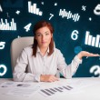 Young businesswoman sitting at desk with diagrams and statistics — Stock Photo