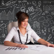 Businesswomsitting at desk with business scheme and icons — Stock Photo #24334107