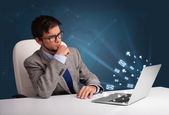 Young man sitting at dest and typing on laptop with message icon — Stok fotoğraf