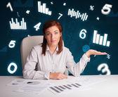 Junge geschäftsfrau sitzen am schreibtisch mit diagrammen und statistiken — Stockfoto