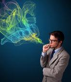 Handsome man smoking cigarette with colorful smoke — Stock Photo