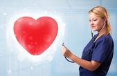 Młoda pielęgniarka uzdrowienie czerwone serce — Zdjęcie stockowe
