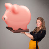 Young girl holding a huge savings piggy bank — Stock Photo