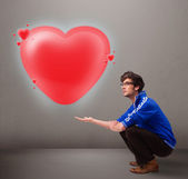 Young man holding lovely 3d red heart — Stock Photo