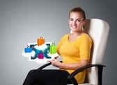 Donna con moderni tablet con colorate shopping bag su nuvola — Foto Stock
