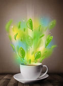 Tea cup with leaves and colorful abstract lights — Stock Photo