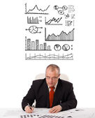 Podnikatel sedí u stolu s statistiky a grafy — Stock fotografie