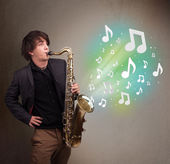 Young musician playing on saxophone while musical notes explodin — Stock Photo