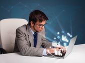 Young man sitting at desk and typing on laptop with diagrams and — Foto Stock