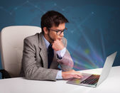 Handsome man sitting at desk and typing on laptop with abstract — Stock Photo