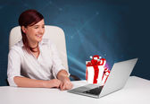Pretty lady sitting at desk and typing on laptop with present bo — Stock Photo
