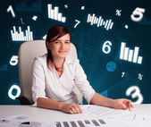 Joven empresaria sentado en el escritorio con los diagramas y estadísticas — Foto de Stock