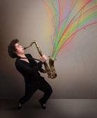 Attractive musician playing on saxophone while colorful abstract — Stock Photo