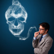 Young man smoking dangerous cigarette with toxic skull smoke — Stock Photo #24915753