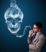 Young man smoking dangerous cigarette with toxic skull smoke — Stock Photo