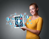 Young woman holding tablet with social network icons — Stockfoto