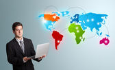 Young man holding a laptop and presenting colorful world map — Stock Photo