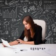 Businesswomsitting at desk with business scheme and icons — Stock Photo #25149493