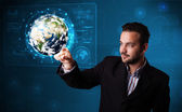 Young businessman touching high-tech 3d earth panel — Stock Photo