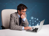 Young man sitting at desk and typing on laptop with social netwo — Stock Photo
