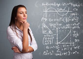 Beautiful school girl thinking about complex mathematical signs — Stock Photo