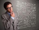 Attractive man looking at stock market graphs and symbols — Stock Photo